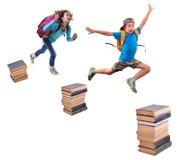 Alumnos con las mochilas que saltan sobre pilas de libros Foto de archivo