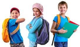 Alumnos de la escuela primaria con la mochila y los libros Foto de archivo libre de regalías