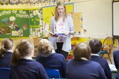 Alumnos de la escuela primaria de Teaching Lesson To del profesor Imágenes de archivo libres de regalías