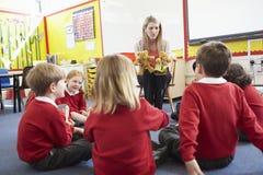 Alumnos de la escuela primaria de Telling Story To del profesor Imagen de archivo
