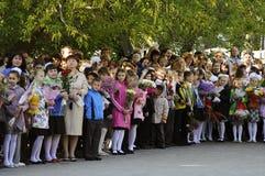 Alumnos de la escuela primaria en una regla solemne el 1 de septiembre adentro Imagen de archivo