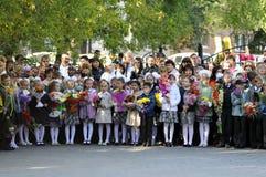 Alumnos de la escuela primaria en una regla solemne el 1 de septiembre adentro Imagen de archivo libre de regalías