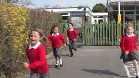 Alumnos de la escuela primaria que corren en patio metrajes