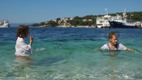 Alumnos de vacaciones, resto en los Balcanes Agua de mar pura, dos niños felices en el fondo de una ciudad mediterránea almacen de video