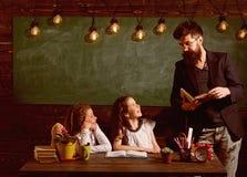 Alumnos del profesor y de las muchachas en la sala de clase, pizarra en fondo El hombre con la barba ense?a a las colegialas, lib foto de archivo libre de regalías