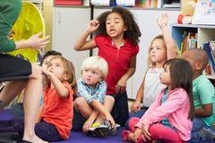 Alumnos elementales en sala de clase que aprenden decir el tiempo Imagen de archivo libre de regalías