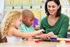 Alumnos elementales que cuentan con el profesor In Classroom imagenes de archivo