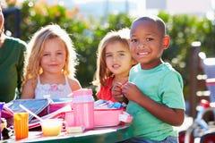 Alumnos elementales que se sientan en la tabla que come el almuerzo Fotografía de archivo libre de regalías