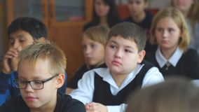 Alumnos en la sala de clase que se sienta en sus escritorios y escuchar el profesor metrajes