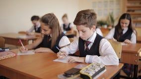 Alumnos en uniforme escolar en la sala de clase en la lección metrajes
