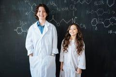 Alumnos encantadores que disfrutan de la lección de la química en el laboratorio Fotos de archivo libres de regalías