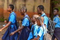 Alumnos ghaneses no identificados en uniforme escolar en pueblo local foto de archivo