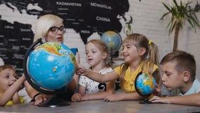 Alumnos hermosos y miradas del profesor en los globos en sala de clase de la geografía en la lección en la escuela primaria Mucha almacen de metraje de vídeo