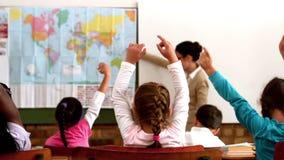 Alumnos jovenes que aumentan las manos durante la lección de la geografía en sala de clase almacen de video
