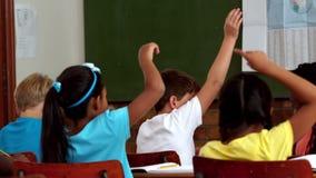 Alumnos jovenes que aumentan las manos durante la lección en sala de clase almacen de video
