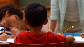Alumnos lindos en sala de clase en la escuela almacen de video