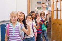 Alumnos lindos que agitan en la cámara en sala de clase Imagenes de archivo