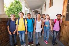 Alumnos lindos que caminan abajo del pasillo Fotos de archivo