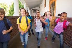 Alumnos lindos que corren abajo del pasillo Fotografía de archivo