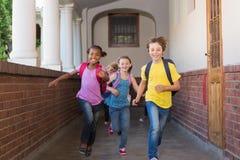 Alumnos lindos que corren abajo del pasillo Imágenes de archivo libres de regalías