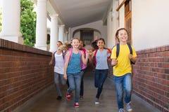 Alumnos lindos que corren abajo del pasillo Fotografía de archivo libre de regalías