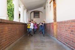 Alumnos lindos que corren abajo del pasillo Imagen de archivo libre de regalías