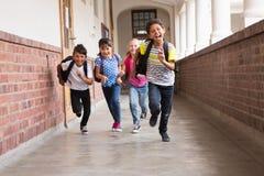 Alumnos lindos que corren abajo del pasillo Fotos de archivo libres de regalías