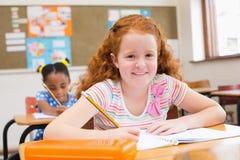 Alumnos lindos que escriben en el escritorio en sala de clase Foto de archivo libre de regalías