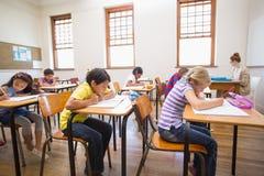 Alumnos lindos que escriben en el escritorio en sala de clase Fotografía de archivo libre de regalías
