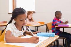 Alumnos lindos que escriben en el escritorio en sala de clase Fotos de archivo