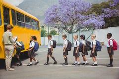 Alumnos lindos que esperan para conseguir en el autobús escolar Fotografía de archivo