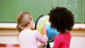 Alumnos lindos que miran un globo Foto de archivo libre de regalías