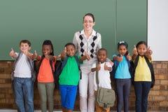 Alumnos lindos que sonríen en la cámara en la sala de clase que muestra los pulgares para arriba Imágenes de archivo libres de regalías