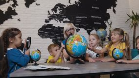 Alumnos lindos y miradas del profesor en los globos en sala de clase de la geografía en la escuela primaria Muchachos, muchachas  metrajes