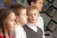 Alumnos primarios que se colocan en sala de clase Foto de archivo libre de regalías