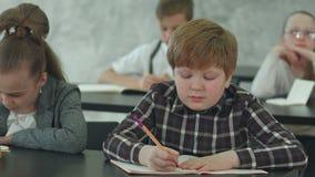 Alumnos que anotan la información en los cuadernos dusring la lección almacen de video