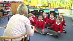 Alumnos que copian las acciones del profesor mientras que canta la canción almacen de metraje de vídeo