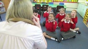 Alumnos que copian las acciones del profesor mientras que canta la canción almacen de video