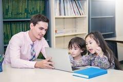 Alumnos que estudian con el profesor que usa el dispositivo del ordenador en sala de clase Fotos de archivo