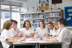 Alumnos que estudian en biblioteca de escuela Foto de archivo libre de regalías