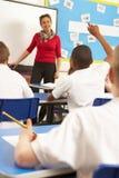 Alumnos que estudian en sala de clase con el profesor Foto de archivo libre de regalías