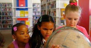 Alumnos que miran el globo en la biblioteca escolar 4k almacen de video