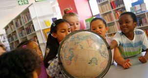 Alumnos que miran el globo en la biblioteca escolar 4k metrajes
