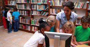 Alumnos que miran el ordenador en biblioteca con su profesor almacen de video