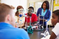 Alumnos que realizan el experimento en clase de la ciencia Foto de archivo libre de regalías