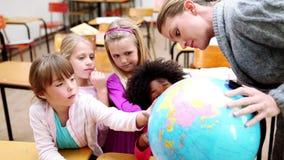 Alumnos que señalan en un globo almacen de metraje de vídeo
