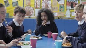 Alumnos que se sientan en la tabla que come el almuerzo almacen de video