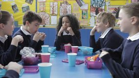Alumnos que se sientan en la tabla que come el almuerzo lleno almacen de video