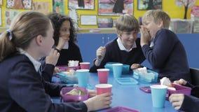 Alumnos que se sientan en la tabla que come el almuerzo lleno metrajes