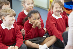 Alumnos que se sientan en Mat Listening To Teacher fotos de archivo